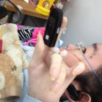 人差し指にはめた小さなマウスをカメラに向かってかざして見せてくれる日野さんの写真